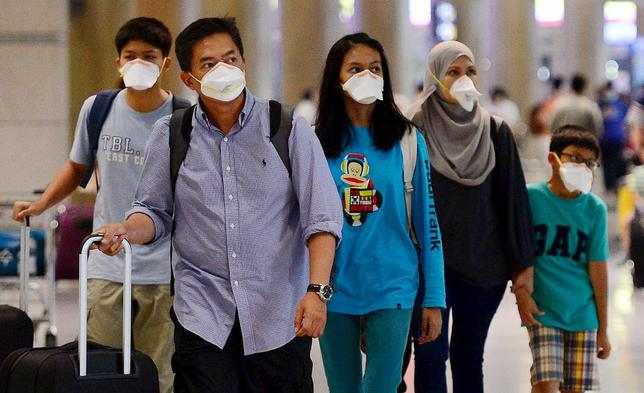 Tourists wearing masks to prevent themselves from contracting Middle East Respiratory Syndrome (MERS) arrive at the Incheon International Airport in Incheon, South Korea, June 7, 2015. REUTERS/Park Ji-hye/News1