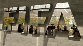 Journalists are reflected in a logo at the FIFA headquarters after a meeting of the executive committee in Zurich October 4, 2013.  REUTERS/Arnd Wiegmann/Files