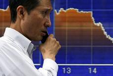 Un hombre usando su celular camina junto a una gráfica que muestra la variación del índice Nikkei, afuera de una agencia de la bolsa, en Tokyo, 9 de junio de 2015. El índice Nikkei de la bolsa de Tokio anotó el martes su mayor pérdida en casi un mes, debilitado por la perspectiva de un alza temprana en las tasas de interés en Estados Unidos y la incertidumbre sobre si Grecia podrá alcanzar un acuerdo con sus acreedores y evitar un default. REUTERS/Issei Kato