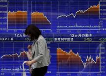 Una mujer camina frente a un tablero electrónico que muestra las variaciones del índice Nikkei, afuera de una agencia de la bolsa, en Tokyo, 9 de junio de 2015. Las bolsas de Asia rebotaban el miércoles desde mínimos en tres meses, aunque el espectro de mayores costos de crédito en Estados Unidos y la preocupación por la aparente falta de avances en las negociaciones entre Grecia y sus acreedores debilitaban la confianza. REUTERS/Issei Kato