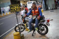 Un conductor de Moto Taxi espera por clientes en el centro de Caracas, 25 de octubre de 2013. Venezuela revivirá un mecanismo cambiario conocido como Sicad, con la subasta de 350 millones de dólares destinados a dar oxígeno al alicaído sector del transporte, anunció el martes el presidente Nicolás Maduro. REUTERS/Jorge Silva