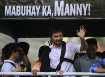 Boxer Manny Pacquiao waves to the crowds during a motorcade in Manila May 13, 2015, after arrving from Las Vegas.    REUTERS/Romeo Ranoco