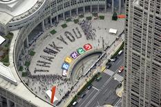 "An aerial view shows people sitting in formation to the words ""thank you"" and displaying signs that collectively read ""Arigato"" (Thank You) during an event celebrating Tokyo being chosen to host the 2020 Olympic Games, at Tokyo Metropolitan Government Building in Tokyo, in this photo taken by Kyodo September 8, 2013. MANDATORY CREDIT.  REUTERS/Kyodo"
