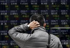 Un peatón se rasca la cabeza mientras mira un tablero electrónico que muestra los distintos índices de precios de las acciones afuera de una agencia de la bolsa, en Tokyo, 10 de abril de 2015. El índice Nikkei de la bolsa de Tokio subió el viernes en una sesión volátil donde los inversores se mostraron cautelosos tras otro giro negativo en las negociaciones sobre la deuda de Grecia. REUTERS/Yuya Shino