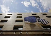 Una bandera de la Unión Europea (izqda.) junto a una de Grecia en la puerta del banco central en Atenas, 11 de junio de 2015. Representantes de alto rango de la UE debatieron formalmente por primera vez sobre una posible cesación de pagos de la deuda griega, mientras las negociaciones entre Atenas y sus acreedores se estancaron antes de que se cumpla un plazo de desembolso a fin de mes, dijeron varios funcionarios a Reuters. REUTERS/Yannis Behrakis