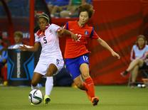 Jun 13, 2015; Montreal, Quebec, CAN; Costa Rica defender Diana Saenz (5) and Korea Republic forward Yoo Younga (12) battle for control of the ball during the second half of a Group E soccer match in the 2015 FIFA women's World Cup at Olympic Stadium. Jean-Yves Ahern-USA TODAY Sports
