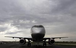 Самолет Sukhoi Superjet 100 на авиасалоне  в Фарнборо, Великобритания 8 июля 2012 года. Российская компания Гражданские самолеты Сухого (ГСС) привезет с авиасалона в Париже контракт на продажу трех самолетов Sukhoi Superjet 100 авиакомпании Якутия, сообщили обе компании. REUTERS/Luke MacGregor