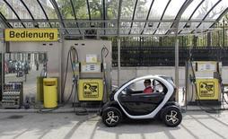 Мужчина паркует электромобиль у обычной заправки в Вене 19 апреля 2012 года. Канцлер Германии Ангела Меркель сообщила в понедельник, что ее правительство размышляет, какими еще мерами подстегнуть спрос на электромобили и надеется принять решение к концу года. REUTERS/Herwig Prammer