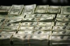 """Пачки долларовых банкнот. Мехико, 22 ноября 2011 года. Глобальные инвесторы переводят активы из акций в наличность в ожидании повышения ставок ФРС США и на фоне опасений дефолта Греции и """"пузыря"""" на фондовом рынке Китая, свидетельствует опрос Bank of America Merrill Lynch. REUTERS/Bernardo Montoya"""
