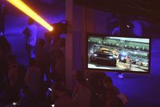 """Pessoas assistindo apresentação da versão beta de """"Battlefield: Hardline"""" durante conferência em Los Angeles.    09/06/2014     REUTERS/David McNew"""