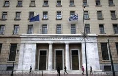 Una bandera de la Unión Europea y una bandera de Grecia, ondean mientras personas caminan junto al edificio del Banco de Grecia, en Atenas, 9 de febrero de 2015. Un alto funcionario de la Unión Europea dijo el miércoles que el no pago de Grecia de una deuda de 1.600 millones de euros (1.800 millones de dólares) al Fondo Monetario Internacional el 30 de junio no provocaría un default sobre préstamos de la zona euro. REUTERS/Alkis Konstantinidis