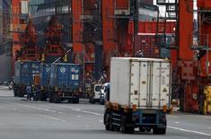 Personas trabajando cerca de contenedores cargados en camiones, en un puerto en Tokyo, 17 de junio de 2015. El crecimiento de las exportaciones de Japón se ralentizó por segundo mes consecutivo en mayo, y la debilidad de la demanda externa ahora amenaza con erosionar el crecimiento económico en el trimestre actual. REUTERS/Yuya Shino