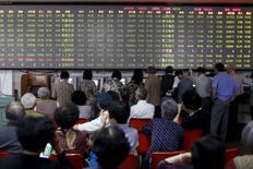 Inversores mirando las pantallas que muestran la información de las acciones, en una agencia de la bolsa en Shanghái, China, 28 de mayo de 2015. Un índice de acciones en Asia subía el jueves y el dólar bajaba ligeramente después de que la Reserva Federal de Estados Unidos sugirió que las tasas de interés subirían más lentamente de lo que los mercados esperaban. REUTERS/Aly Song