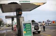 Un trabajador espera por clientes en una gasolinera Petrobras, en Río de Janeiro, 10 de diciembre de 2014. La petrolera estatal brasileña Petrobras está importando nuevamente gasolina y vendiéndola localmente con pérdidas, pero una menor demanda significa que será difícil ajustar el precio para que esté en línea con los niveles internacionales, dijo una fuente a Reuters. REUTERS/Ricardo Moraes