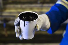 A worker holds a cup of heavy oil before it is shipped to the market at a facility south of Fort McMurray, Alberta, August 15, 2013. REUTERS/Todd Korol