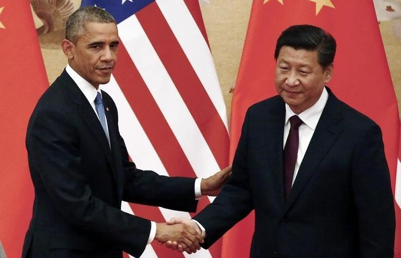 U.S. President Barack Obama (L) shakes hands with China's President Xi Jinping in front of U.S. and Chinese national flags during a joint news conference at the Great Hall of the People in Beijing November 12, 2014. REUTERS/Petar Kujundzic
