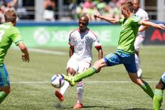Jun 20, 2015; Seattle, WA, USA; San Jose Earthquakes midfielder Sanna Nyassi (17) passes while under pressure from Seattle Sounders FC defender Dylan Remick (15) during the first half at CenturyLink Field. San Jose defeated Seattle, 2-0. Mandatory Credit: Joe Nicholson-USA TODAY Sports