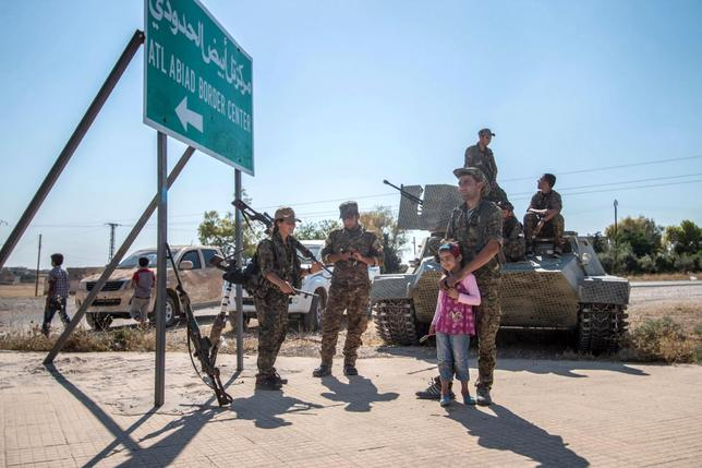 Fighters of the Kurdish People's Protection Units (YPG) stand with children near a sign in Tel Abyad town, Raqqa governorate, June 16, 2015.  REUTERS/Rodi Said