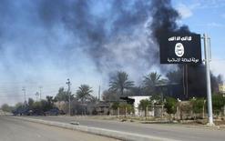 Un bandera del Estado Islámico flameando frente a una columna de humo tras la toma de Saadiya a manos de fuerzas de seguridad iraquíes y chiíes, nov 24 2014. Una unidad de policía a nivel europeo se formará el próximo mes con el objetivo de cerrar las cuentas empleadas por militantes de Estado Islámico en las redes sociales para difundir propaganda y reclutar extranjeros para su causa, dijo Europol el lunes.  REUTERS/Stringer