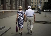 Пожилая пара в Москве 17 августа 2013 года. Банк России считает, что решение правительства о сохранении накопительной части пенсии и возобновление механизма с 2016 года обеспечит стабильный приток длинных денег в экономику страны, а также будет способствовать снижению волатильности на российском фондовом рынке. REUTERS/Lucy Nicholson