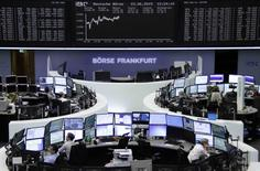 Traders are pictured at their desks in front of the DAX board at the Frankfurt stock exchange June 23, 2015.     REUTERS/Remote/Staff