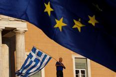 Manifestante agita bandeira da Grécia na entrada do Parlamento durante protesto, em Atenas. 22/06/2015 REUTERS/Yannis Behrakis