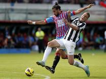 Zagueiro Nicolás Spolli do Catania (camisa vermelha e azul) durante partida contra a Juventus.  28/10/2012   REUTERS/Alessandro Bianchi