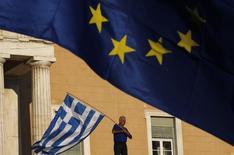Участник акции протеста с флагом Греции на фоне флага ЕС в Афинах 22 июня 2015 года. Переговоры о решение долговых проблем Греции продолжаются, и встреча премьера Алексиса Ципраса и группы международных кредиторов в Брюсселе состоится, как и было запланировано, сообщил чиновник ЕС, знакомый с ходом переговоров. REUTERS/Yannis Behrakis