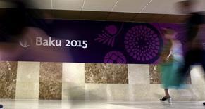 Люди проходят мимо рекламного плаката Европейских игр в Баку 11 июня 2015 годаБританец, нанятый организаторами помпезного открытия и других шоу на Европейских играх в Баку, погиб в результате ДТП, через две недели после того, как при похожих обстоятельствах были травмированы юные австрийские спортсменки.  REUTERS/Stoyan Nenov