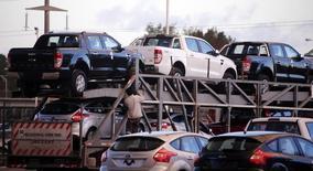 Un camión cargado con vehículos nuevos en la planta de Ford en Buenos Aires, mayo 22 2014. La economía de Argentina habría mejorada en el cuarto mes del año apoyada por el buen rendimiento en el sector de la construcción y del segmento agropecuario, según un sondeo de Reuters publicado el miércoles.    REUTERS/Marcos Brindicci