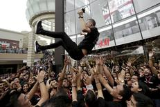 A worker of Hennes & Mauritz (H&M) is thrown in the air by colleagues during the inauguration of the first H&M store in Peru, at the Jockey Plaza mall in Lima, in this May 9, 2015 file photo. REUTERS/Mariana Bazo/Files
