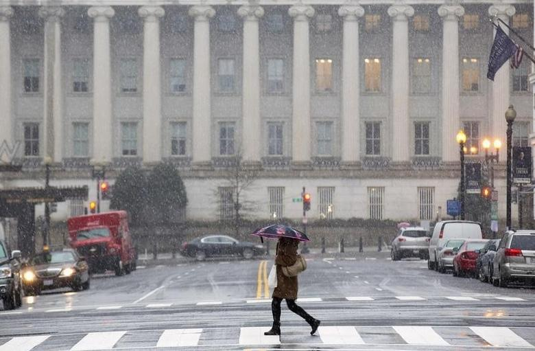 A woman crosses a nearly empty street at rush hour, near the U.S. Treasury Building during a snow storm in Washington March 5, 2015. REUTERS/Joshua Roberts