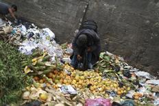 Un hombre recoge naranjas en un basural de La Terminal, uno de los mercados npas grandes en Ciudad de Guatemala, 27 de febrero de 2015. Las principales compañías de alimentos y bebidas del mundo han prometido reducir a la mitad para 2025 la cantidad de comida que malgastan, tratando de anticiparse a la regulación gubernamental motivada por la preocupación acerca de los costos ambientales, económicos y sociales provocados por tal ineficiencia. REUTERS/Jorge Dan Lopez