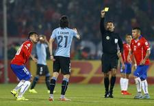 Referee Sandro Ricci shows a second yellow card to Uruguay's Edinson Cavani as Chile's Gonzalo Jara (18) looks on during their quarter-finals Copa America 2015 soccer match at the National Stadium in Santiago, Chile, June 24, 2015. REUTERS/Ivan Alvarado