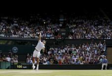 Roger Federer of Switzerland serves during his men's singles semi-final tennis match against Milos Raonic of Canada at the Wimbledon Tennis Championships, in London in this July 4, 2014 file photo.    REUTERS/Stefan Wermuth/Files