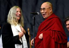 Patti Smith (L) shares a light moment with the Dalai Lama as she performs on the Pyramid stage at Worthy Farm in Somerset during the Glastonbury Festival in Britain, June 28, 2015.  REUTERS/Dylan Martinez