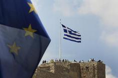 A European Union flag flutters as tourists gather around a Greek flag atop the Acropolis hill in Athens, Greece June 26, 2015.  REUTERS/Yannis Behrakis