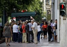 File d'attente devant un distributeur de billets à Athènes. La Bourse d'Athènes et les banques grecques demeureront fermées lundi après l'échec des négociations entre la Grèce et ses créanciers internationaux ce week-end, selon une source financière et le directeur général de la Piraeus Bank. /Photo prise le 28 juin 2015/REUTERS/Yannis Behrakis