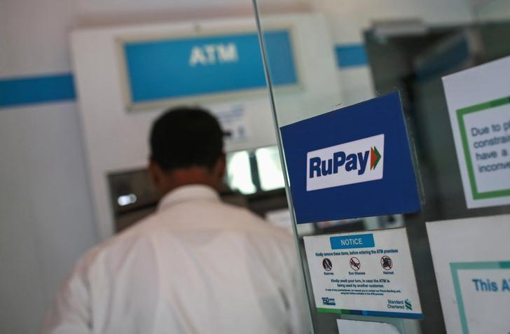 A RuPay sign is seen on the door of an automated teller machine (ATM) while a user is seen, at a commercial building in Mumbai September 11, 2014. REUTERS/Danish Siddiqui/Files