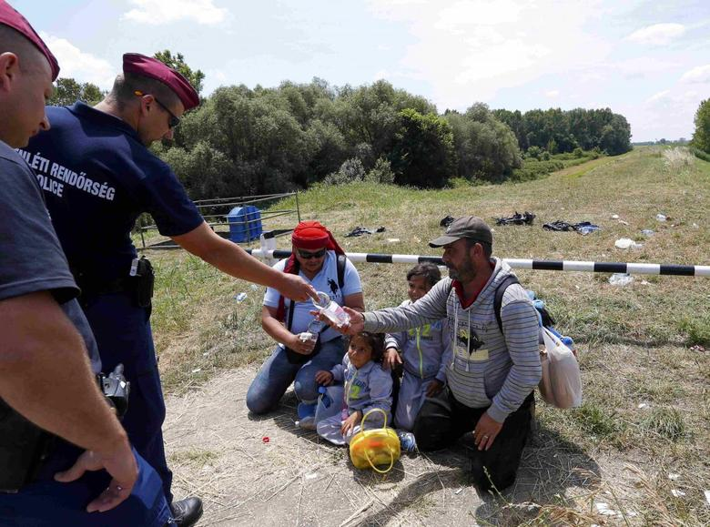 Hungarian police give water to migrants from Syria who crossed the border from Serbia to Hungary, walking on the dam near the Tisza river near the city of Szeged, Hungary, on June 29, 2015. REUTERS/Laszlo Balogh