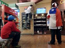 Empleados del supermercado miran el partido entre Chile y México, por la Copa América, en La Serena, Chile, 15 de junio de 2015. Las ventas reales de los supermercados en Chile crecieron un 5,0 por ciento interanual en mayo, principalmente por efectos de tipo calendario y un mayor dinamismo en el rubro de vestuario, calzados y accesorios, según datos difundidos el martes por el Gobierno. REUTERS/Marcos Brindicci