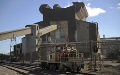 Una locomotora pasa junto a una acería en Concepción, Chile, dic 5 2014. La producción manufacturera en Chile se contrajo un 3,3 por ciento en mayo, en una variación más profunda a la esperada y que se enmarca dentro del débil desempeño mostrado por la actividad económica en la primera mitad de este año. REUTERS/Jose Luis Saavedra