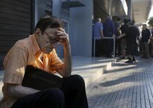 """Giorgos, un pensionado ateniense de 77 años, sentado a las afueras de una sucursal del Banco Nacional de Grecia a la espera de poder recibir el pago de su jubilación, jun 29 2015. Grecia pidió a sus acreedores extender por """"un corto periodo de tiempo"""" su actual programa de rescate para evitar un impago de deuda hasta que entre en vigencia un nuevo paquete de asistencia financiera, según una carta enviada por el primer ministro Alexis Tsipras y publicada el martes por el sitio web Politico.  REUTERS/Yannis Behrakis"""