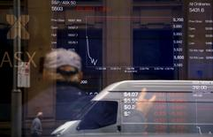 A man gestures as he looks at boards displaying stock prices at the Australian Securities Exchange in central Sydney, Australia June 29, 2015. REUTERS/David Gray