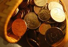 Рублевые монеты в магазине Красноярска 12 января 2015 года. Рубль дешевеет в начале первых июльских торгов вслед за нефтью и в условиях возможного снижения активности экспортеров после уплаты июньских налогов, при этом против играют также покупки валюты Центробанком и сезонная конвертация дивидендных выплат. REUTERS/Ilya Naymushin
