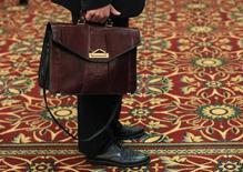 Un hombre sostiene su maletín mientras espera en una feria de empleos en Melville, Nueva York, 19 de julio de 2012. Los empleadores privados de Estados Unidos sumaron 237.000 empleos en junio, la mayor alza desde diciembre, sugiriendo una mejora adicional en el mercado de trabajo que podría habilitar a la Reserva Federal a subir las tasas este año, mostró el miércoles un reporte de una firma de procesamiento de datos. REUTERS/Shannon Stapleton
