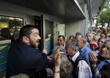 Gerente de banco tenta explicar situação a centenas de pensionistas em fila do lado de fora do Banco Nacional, em Atenas. 01/07/2015 REUTERS/Yannis Behrakis