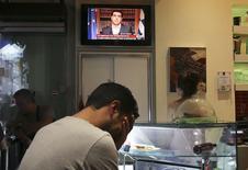 Una persona reacciona a un discurso televisado del primer ministro griego, Alexis Tsipras, en un café de Atenas, jul 1 2015. Los inversores estadounidenses esperan que los griegos respalden, en un referendo del 5 de julio, la propuesta de fondos a cambio de reformas que hicieron los acreedores del país, según un sondeo de Reuters realizado esta semana.  REUTERS/Alkis Konstantinidis
