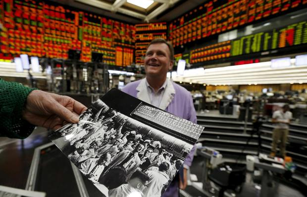 Thomas Cashman looks at some old family photos belonging to John Pietrzak (R) on the Chicago Board of Trade grain trading floor in Chicago, Illinois, United States, June 9, 2015.  REUTERS/Jim Young