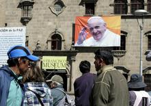 Pedestrians walk at San Francisco square where an image of Pope Francis is displayed in La Paz June 30, 2015. REUTERS/David Mercado